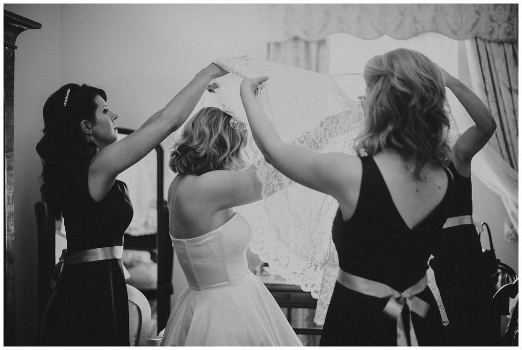 bridemaids help bride get into her wedding dress at Castle Grove Country House