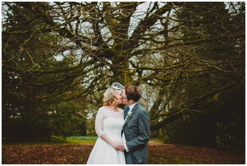 bride and groom share a kiss under a tree at Castle Grove Country House