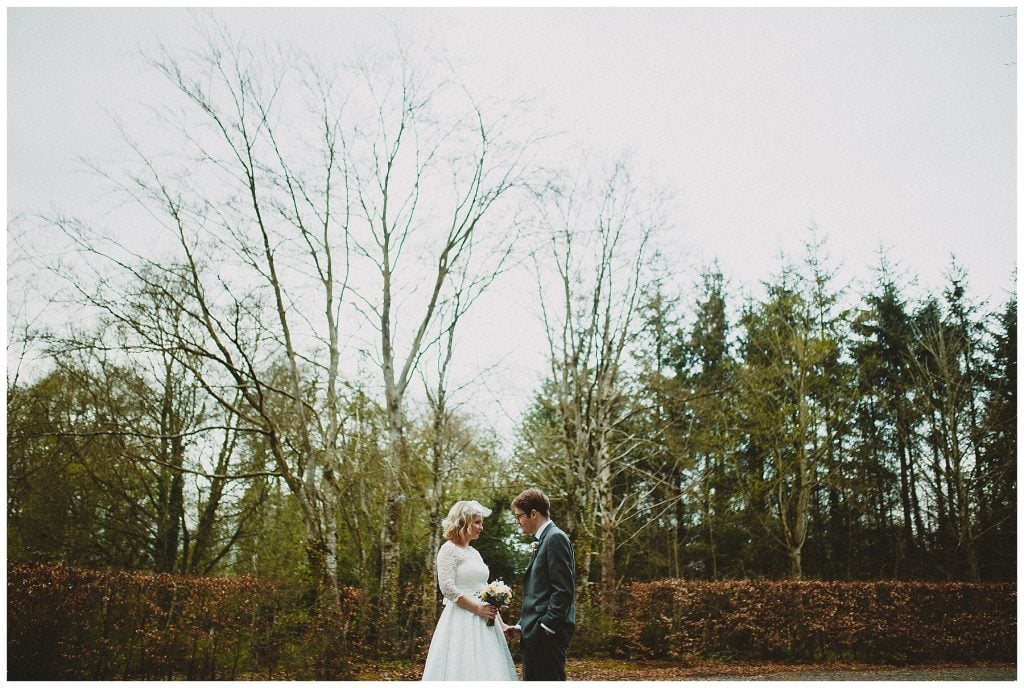 bride and groom pose in front of trees for wedding portraits at Castle Grove Country House
