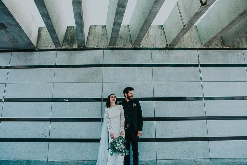 bride and groom laugh under the bridge by the Walled City Brewery in Derry